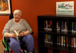 Picture of a woman in a wheelchair sitting next to a bookcase of books
